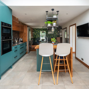 Design ideas for a mid-sized contemporary galley eat-in kitchen in Other with a drop-in sink, turquoise cabinets, quartzite benchtops, metallic splashback, slate splashback, stainless steel appliances, porcelain floors, white floor and multi-coloured benchtop.