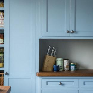 Geschlossene, Zweizeilige, Mittelgroße Klassische Küche ohne Insel mit Landhausspüle, Schrankfronten im Shaker-Stil, blauen Schränken, Arbeitsplatte aus Holz, Küchenrückwand in Weiß, Küchengeräten aus Edelstahl, Travertin und beigem Boden in Edinburgh