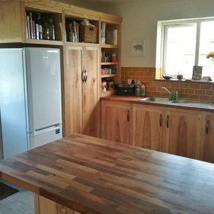 他の地域の大きいラスティックスタイルのおしゃれなキッチン (ダブルシンク、シェーカースタイル扉のキャビネット、中間色木目調キャビネット、木材カウンター、オレンジのキッチンパネル、磁器タイルのキッチンパネル、ラミネートの床、グレーの床、茶色いキッチンカウンター) の写真
