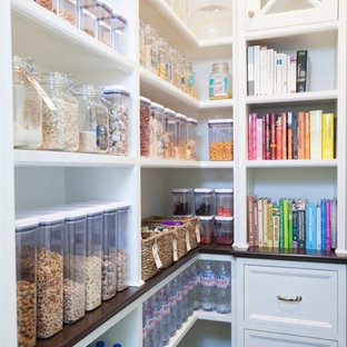 Design ideas for a medium sized traditional l-shaped kitchen pantry in London with dark hardwood flooring, black floors, recessed-panel cabinets and brown worktops.