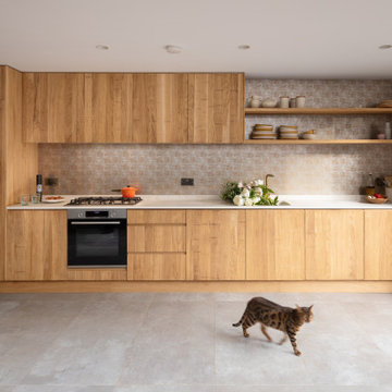 Bespoke kitchen with band-sawn cabinetry and golden glass splashback
