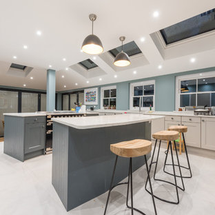 This is an example of a large classic l-shaped kitchen in Surrey with a submerged sink, recessed-panel cabinets, multiple islands, beige cabinets, green splashback, black appliances, beige floors and beige worktops.