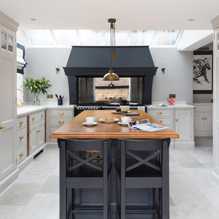 Design ideas for a medium sized traditional u-shaped kitchen in London with recessed-panel cabinets, grey cabinets, metallic splashback, mirror splashback, an island and grey floors.
