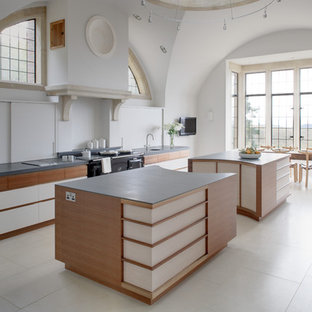 Large modern l-shaped open plan kitchen in Surrey with medium wood cabinets, granite worktops and multiple islands.