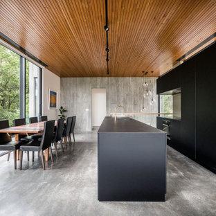 Modelo de cocina comedor en L, minimalista, grande, con fregadero integrado, armarios con paneles lisos, puertas de armario negras, salpicadero metalizado, electrodomésticos de acero inoxidable, una isla, suelo gris y encimeras negras