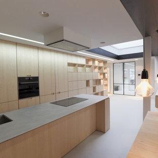 Foto de cocina en U, moderna, grande, con fregadero de doble seno, puertas de armario amarillas, encimera de cemento, electrodomésticos con paneles, suelo de terrazo, una isla, suelo gris y encimeras grises