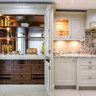 Traditional kitchen pantry in Berkshire with recessed-panel cabinets, beige cabinets, stone slab splashback, black appliances, beige floors and grey worktops.