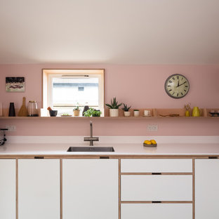 Scandinavian l-shaped kitchen in London with a single-bowl sink, flat-panel cabinets, white cabinets, pink splashback, white worktops and composite countertops.