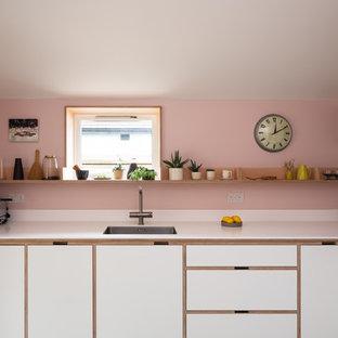 ロンドンの北欧スタイルのおしゃれなL型キッチン (シングルシンク、フラットパネル扉のキャビネット、白いキャビネット、ピンクのキッチンパネル、白いキッチンカウンター、人工大理石カウンター) の写真