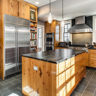 Photo of a country kitchen in Dallas with flat-panel cabinets, medium wood cabinets, grey splashback, stainless steel appliances, with island and slate splashback.