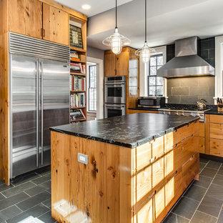 Urige Küche mit flächenbündigen Schrankfronten, hellbraunen Holzschränken, Küchenrückwand in Grau, Küchengeräten aus Edelstahl, Kücheninsel und Rückwand aus Schiefer in Dallas