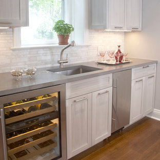 Inspiration for a mid-sized contemporary l-shaped dark wood floor eat-in kitchen remodel in New York with an undermount sink, shaker cabinets, gray cabinets, solid surface countertops, white backsplash, stone tile backsplash, stainless steel appliances and an island