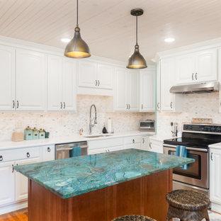 Idéer för ett turkos l-kök, med vita skåp, bänkskiva i kvartsit, rostfria vitvaror, mellanmörkt trägolv och en köksö