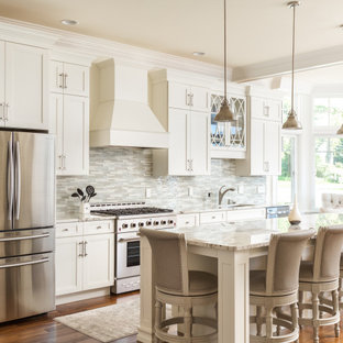 Inspiration for a transitional single-wall eat-in kitchen in New York with white cabinets, quartzite benchtops, stainless steel appliances, medium hardwood floors, with island, yellow benchtop, an undermount sink, shaker cabinets, multi-coloured splashback, metal splashback and brown floor.