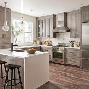 Idéer för ett klassiskt vit u-kök, med en undermonterad diskho, skåp i shakerstil, bruna skåp, vitt stänkskydd, rostfria vitvaror, mörkt trägolv, en halv köksö och brunt golv