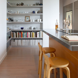 Einzeilige, Mittelgroße Moderne Küche mit Edelstahl-Arbeitsplatte, Waschbecken, flächenbündigen Schrankfronten, hellbraunen Holzschränken, Küchengeräten aus Edelstahl, hellem Holzboden und Kücheninsel in Seattle