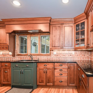 This is an example of a large contemporary galley kitchen pantry in New York with a built-in sink, raised-panel cabinets, medium wood cabinets, laminate countertops, beige splashback, stone tiled splashback, stainless steel appliances, medium hardwood flooring, no island, brown floors and multicoloured worktops.