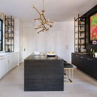 Inredning av ett modernt u-kök, med släta luckor, svarta skåp, integrerade vitvaror, målat trägolv, en köksö och vitt golv