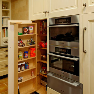 Design ideas for a large arts and crafts u-shaped eat-in kitchen in DC Metro with an undermount sink, beaded inset cabinets, white cabinets, soapstone benchtops, beige splashback, stone tile splashback, panelled appliances, porcelain floors, with island and beige floor.