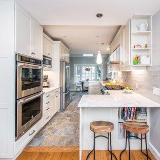 Inspiration för mellanstora moderna vitt kök, med en undermonterad diskho, vita skåp, bänkskiva i kvarts, grått stänkskydd, stänkskydd i tunnelbanekakel, rostfria vitvaror, skiffergolv, en halv köksö, flerfärgat golv och skåp i shakerstil