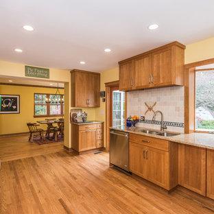 Inspiration för ett stort amerikanskt kök, med en undermonterad diskho, luckor med infälld panel, bruna skåp, granitbänkskiva, beige stänkskydd, stänkskydd i terrakottakakel, rostfria vitvaror, ljust trägolv och brunt golv