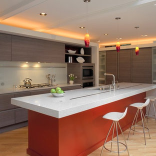 Contemporary kitchen designs - Example of a trendy light wood floor and beige floor kitchen design in DC Metro with flat-panel cabinets, an island, an undermount sink, brown cabinets, white backsplash, glass sheet backsplash and stainless steel appliances