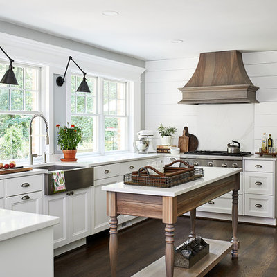 Example of a mid-sized country u-shaped dark wood floor and brown floor eat-in kitchen design in DC Metro with white backsplash, stainless steel appliances, an island, white countertops, a farmhouse sink, recessed-panel cabinets and white cabinets
