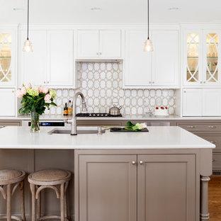 Immagine di una cucina tradizionale di medie dimensioni con ante bianche, paraspruzzi bianco, elettrodomestici in acciaio inossidabile, isola, lavello sottopiano, ante con riquadro incassato e pavimento in legno massello medio