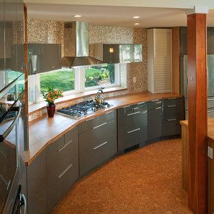 Cette photo montre une cuisine tendance avec un électroménager en acier inoxydable, un plan de travail en bois, un placard à porte plane, des portes de placard grises et une crédence marron.