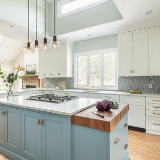 Inspiration pour une grande arrière-cuisine traditionnelle en L avec un placard à porte shaker, des portes de placard bleues, un plan de travail en bois, une crédence bleue, une crédence en carreau de céramique, un électroménager encastrable et un îlot central.