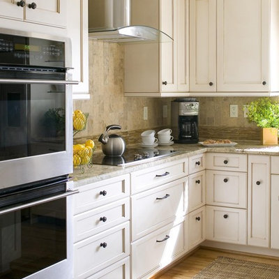 Inspiration for a mid-sized transitional l-shaped medium tone wood floor and brown floor kitchen remodel in DC Metro with stone tile backsplash, beige backsplash, recessed-panel cabinets, an undermount sink, white cabinets, stainless steel appliances and an island