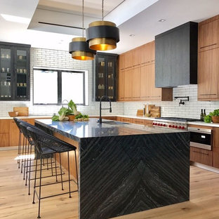 This is an example of a contemporary l-shaped open plan kitchen in Los Angeles with flat-panel cabinets, stainless steel cabinets, white splashback, subway tile splashback, stainless steel appliances and with island.