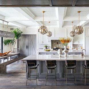 Mediterrane Wohnküche mit Unterbauwaschbecken, Schrankfronten im Shaker-Stil, weißen Schränken, Küchenrückwand in Braun, Küchengeräten aus Edelstahl, dunklem Holzboden, zwei Kücheninseln, braunem Boden, weißer Arbeitsplatte und Kassettendecke in Los Angeles
