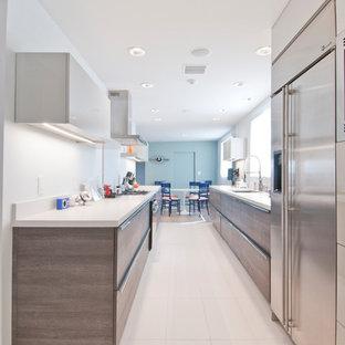 Modern inredning av ett mellanstort kök, med en undermonterad diskho, släta luckor, grå skåp, bänkskiva i kvartsit, rött stänkskydd, klinkergolv i porslin och turkost golv