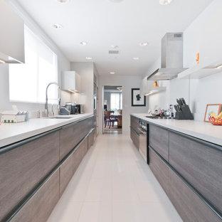 Inredning av ett modernt mellanstort kök, med en undermonterad diskho, släta luckor, grå skåp, bänkskiva i kvartsit, rött stänkskydd, rostfria vitvaror, klinkergolv i porslin och turkost golv
