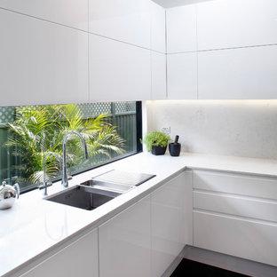 Foto di una piccola cucina parallela contemporanea chiusa con lavello sottopiano, ante lisce, ante bianche, top in quarzo composito, paraspruzzi multicolore, paraspruzzi a specchio, elettrodomestici in acciaio inossidabile, pavimento in marmo e pavimento nero