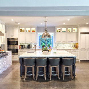 Large traditional eat-in kitchen inspiration - Example of a large classic l-shaped light wood floor and brown floor eat-in kitchen design in Los Angeles with an undermount sink, raised-panel cabinets, white cabinets, stainless steel appliances, an island, granite countertops, gray backsplash, stone slab backsplash and gray countertops