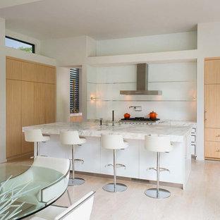 ダラスの広いモダンスタイルのおしゃれなキッチン (アンダーカウンターシンク、フラットパネル扉のキャビネット、淡色木目調キャビネット、大理石カウンター、パネルと同色の調理設備、淡色無垢フローリング、ベージュの床、ターコイズのキッチンカウンター) の写真