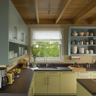 サンフランシスコの中くらいのコンテンポラリースタイルのおしゃれなキッチン (オープンシェルフ、パネルと同色の調理設備、濃色無垢フローリング、アンダーカウンターシンク、緑のキャビネット、黒いキッチンパネル) の写真