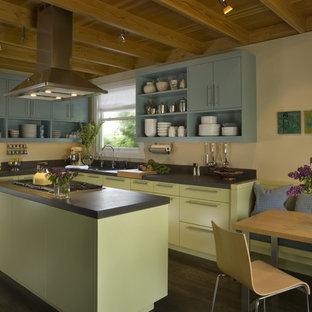 Foto de cocina en L, bohemia, de tamaño medio, abierta, con armarios abiertos, puertas de armario verdes, salpicadero negro, suelo de madera oscura, una isla y fregadero bajoencimera