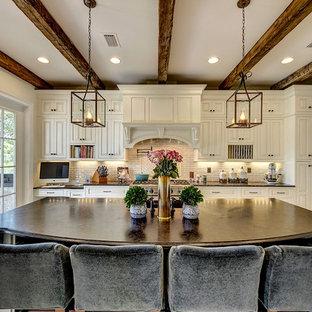 ニューオリンズの大きいトランジショナルスタイルのおしゃれなキッチン (レイズドパネル扉のキャビネット、白いキャビネット、サブウェイタイルのキッチンパネル、アンダーカウンターシンク、御影石カウンター、ベージュキッチンパネル、シルバーの調理設備の、磁器タイルの床) の写真