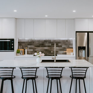 Mid-sized contemporary galley kitchen in Sydney with a drop-in sink, flat-panel cabinets, white cabinets, grey splashback, stainless steel appliances, with island, beige floor and grey benchtop.