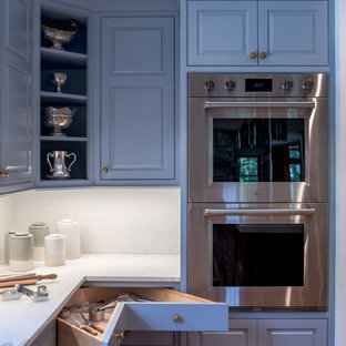 Offene, Mittelgroße Klassische Küche in U-Form mit Landhausspüle, profilierten Schrankfronten, blauen Schränken, Marmor-Arbeitsplatte, Küchenrückwand in Weiß, Küchengeräten aus Edelstahl, hellem Holzboden, Kücheninsel, beigem Boden und weißer Arbeitsplatte in New York