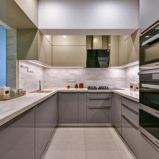 Cette photo montre une cuisine asiatique en U avec un évier encastré, un placard à porte plane, des portes de placard grises, une crédence beige, un électroménager en acier inoxydable, un sol beige et un plan de travail beige.