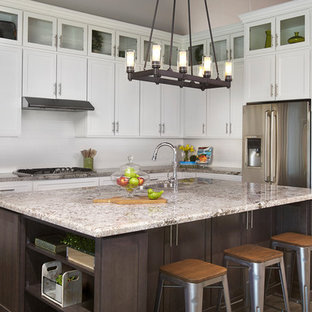 Inspiration for a mid-sized transitional l-shaped dark wood floor kitchen remodel in Phoenix with shaker cabinets, white cabinets, granite countertops, white backsplash, subway tile backsplash, stainless steel appliances, an island and an undermount sink