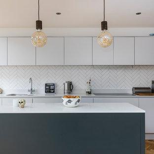 На фото: кухни среднего размера в современном стиле с двойной раковиной, плоскими фасадами, белыми фасадами, белым фартуком, фартуком из керамической плитки, паркетным полом среднего тона и островом