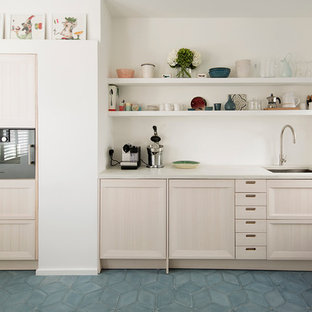Mid-sized scandinavian galley eat-in kitchen in London with a drop-in sink, beaded inset cabinets, light wood cabinets, concrete benchtops, white splashback, cement tile splashback, stainless steel appliances, cement tiles, no island and blue floor.