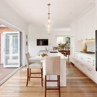Inspiration for a mid-sized transitional single-wall kitchen in Sydney with shaker cabinets, white cabinets, granite benchtops, grey splashback, black appliances, medium hardwood floors, with island, a single-bowl sink and grey benchtop.