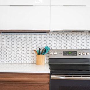 ミネアポリスの中サイズのトランジショナルスタイルのおしゃれなキッチン (アンダーカウンターシンク、フラットパネル扉のキャビネット、白いキャビネット、クオーツストーンカウンター、白いキッチンパネル、磁器タイルのキッチンパネル、シルバーの調理設備の、クッションフロア、茶色い床、白いキッチンカウンター) の写真