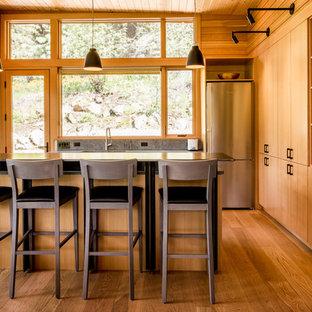 Idéer för ett mellanstort rustikt kök, med en enkel diskho, släta luckor, skåp i mellenmörkt trä, rostfria vitvaror, mellanmörkt trägolv och en köksö